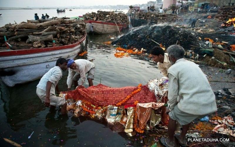 Перед кремацией тело на носилках окунают в реку